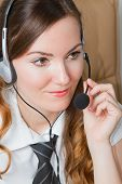 Business Theme:  Portrait Of Successful  Woman Manager With Speakerphone In An Office Environment. M