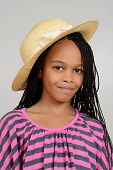 stock photo of cornrow  - Young african girl wearing a straw hat on grey background - JPG