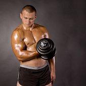 Muscled Male Bodybuilder Dumbbell Swing