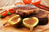 meat entree : grilled beef steak served with red hot cayenne peppers green stuff sweet figs and cutl