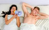 Funny couple in bed waking up in the morning.Using megaphone