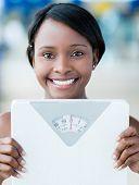 Mujer feliz en el gimnasio con escala de peso