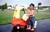 stock photo of car wash  - Young toddler washing his car with a big smile
