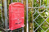 stock photo of postbox  - Traditional old English red postbox hang on gate - JPG