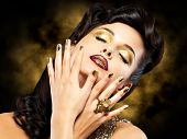stock photo of minx  - Beautiful brunet woman with golden nails over style background - JPG