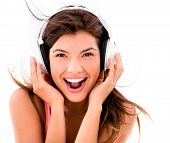 Happy woman listening to music with  headphones �?�¢?? isolated over white