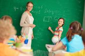 Portrait of smart teacher and schoolgirl standing by blackboard and looking at schoolkids in classro