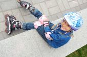 Child With Rollerskates And Protective Helmet And Pads