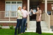 pic of real-estate agent  - Happy couple getting keys to new house from real estate agent - JPG