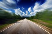 stock photo of horizon  - Chasing the horizon - driving fast on straight road