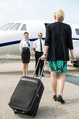 Rear view of businesswoman with luggage walking towards private plane while pilot and airhostess sta
