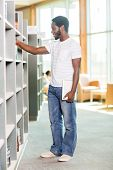 Full length of African American student with digital tablet choosing book in bookstore