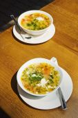 Two Plates Of Chicken Soup On Wooden Table