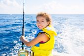 stock photo of life-boat  - blond  kid girl fishing trolling at boat with rod reel and yellow life jacket - JPG