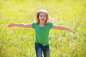 Blond kid girl happy running open hands smiling in outdoor green meadow