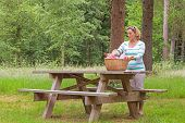 A woman placing a whicker picnic basket full of food and drink on a table in woodland, on a bright s