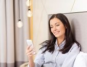 business, technology, internet and hotel concept - happy businesswoman with smartphone lying in hote