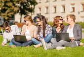 summer, internet, education, technlogy and campus concept - group of students or teenagers with lapt