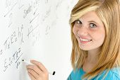Smiling student teenage girl writing mathematics white board looking camera