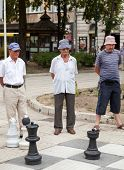 SARAJEVO, BOSNIA AND HERZEGOVINA - AUGUST 11, 2012: Men play chess on street with large chess pieces