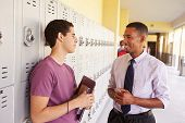 Male High School Student Talking To Teacher By Lockers