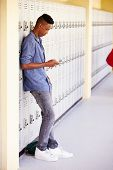 Male High School Student By Lockers Using Mobile Phone