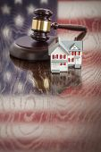 Small House and Gavel on Wooden Table with American Flag Reflection.