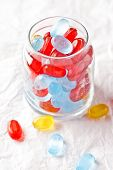 colorful candies in glass jar closeup on white paper background