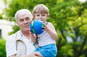 Happy Grandfather Playing With Little Grandchild Ball
