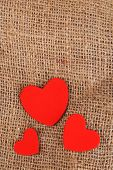 Hearts made of felt on sacking background