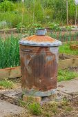 Rusty Garden Incinerator With Plants In Background