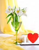 Freesias in glass on table on fabric background