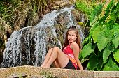 pic of elephant ear  - Teenager girl sitting in an oasis of waterfall pond and  - JPG