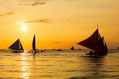 Silhouettes of sailboats over beautiful sunset on Boracay island Philippines