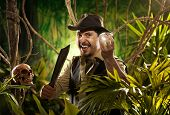 stock photo of machete  - Adventurer with machete finding a huge gem in the jungle with skull on foreground - JPG