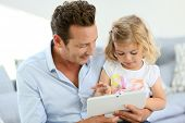 Father and daughter playing with digital tablet