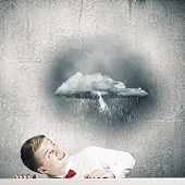 Young man looking above at raining cloud