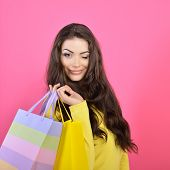 Shopping woman holding bags and gives a wink, isolated on pink studio background.
