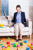pic of superwoman  - Furious woman sitting on a sofa in a room full of kids toys - JPG
