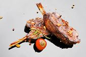 meat savory: roast ribs on black plate with red hot pepper