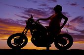 Silhouette Pregnant Woman On Motorcycle Side Hand On Tank