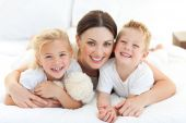 image of pyjama  - Portrait of a happy mother and her children lying on a bed - JPG