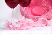 Two Glasses Of Red Wine On A White Background Near Pink Panties And Hat