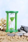 Hourglass in sand on bright background
