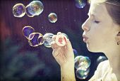 Retro styled photo of young girl blowing soap bubbles
