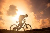 The Silhouette Of Bicycle Rider On The Hill