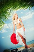Young woman in white bikini holding sarong on windy tropical beach