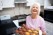 A laughing pensioner holding a tray of baked muffins just out of the oven