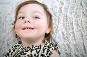 Portrait of smiling little girl in leopard print dress with beads