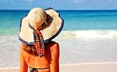 Woman in bikini and hat on tropical beach